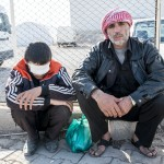 Mohamed Rahmo and his blinded son, Mustafa, on their way back to Syria. Photo: © Elio Germani