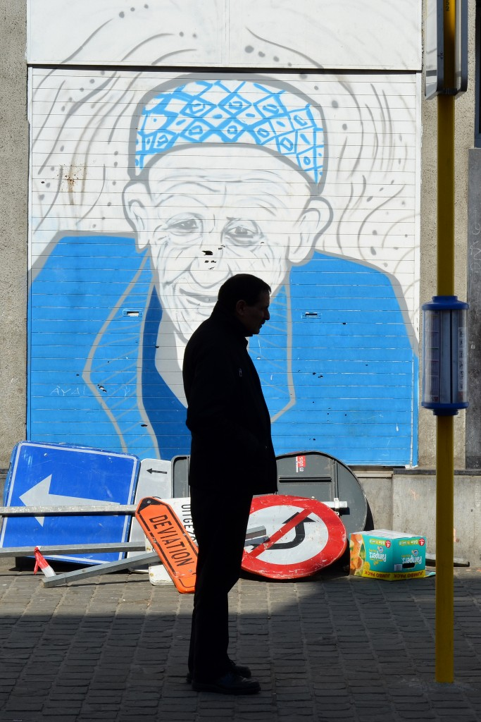 A man stands in front of mural in inner-city Brussels. Photo: ©Simon Blackley